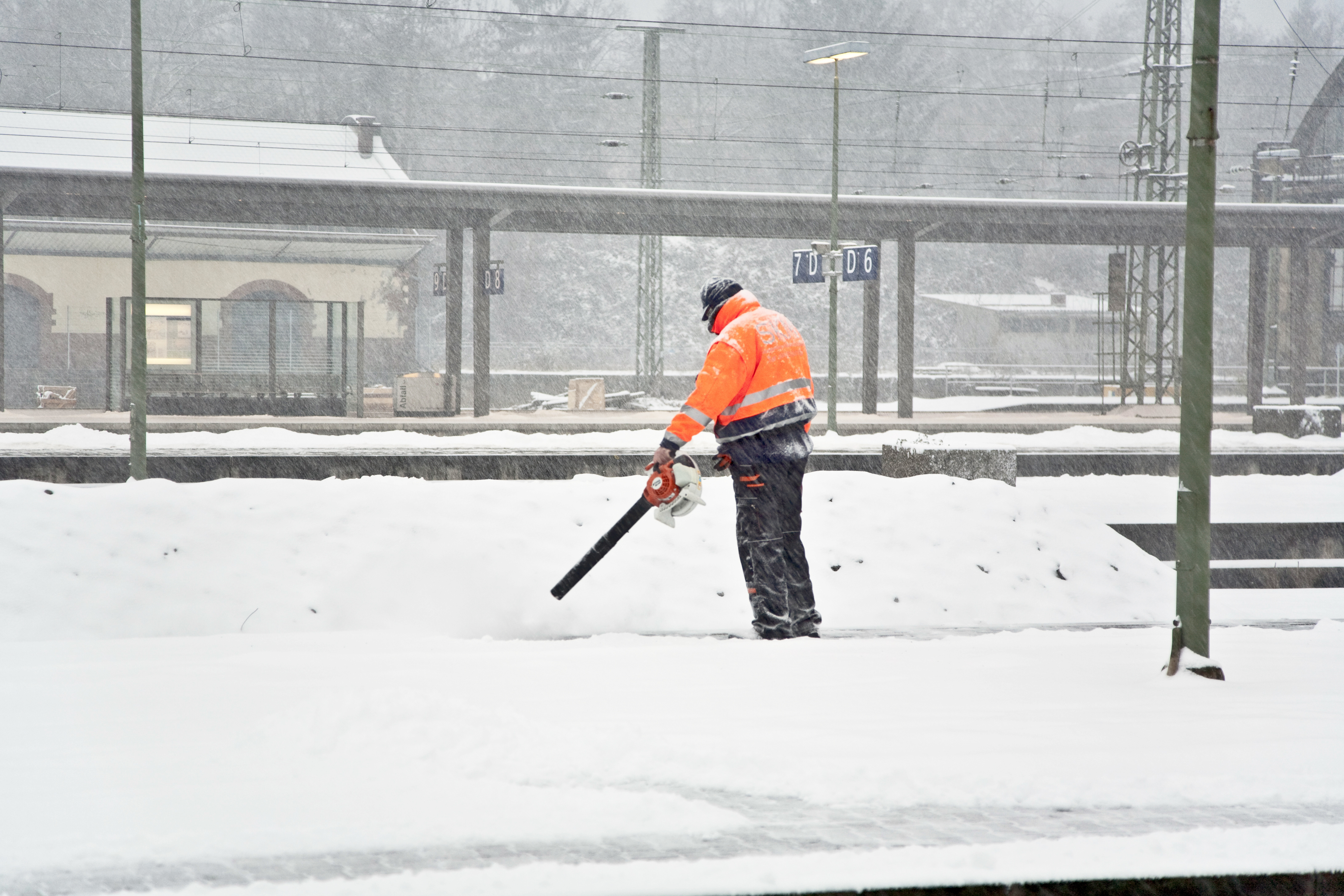 worker is cleaning the platform of a train station fromsnow