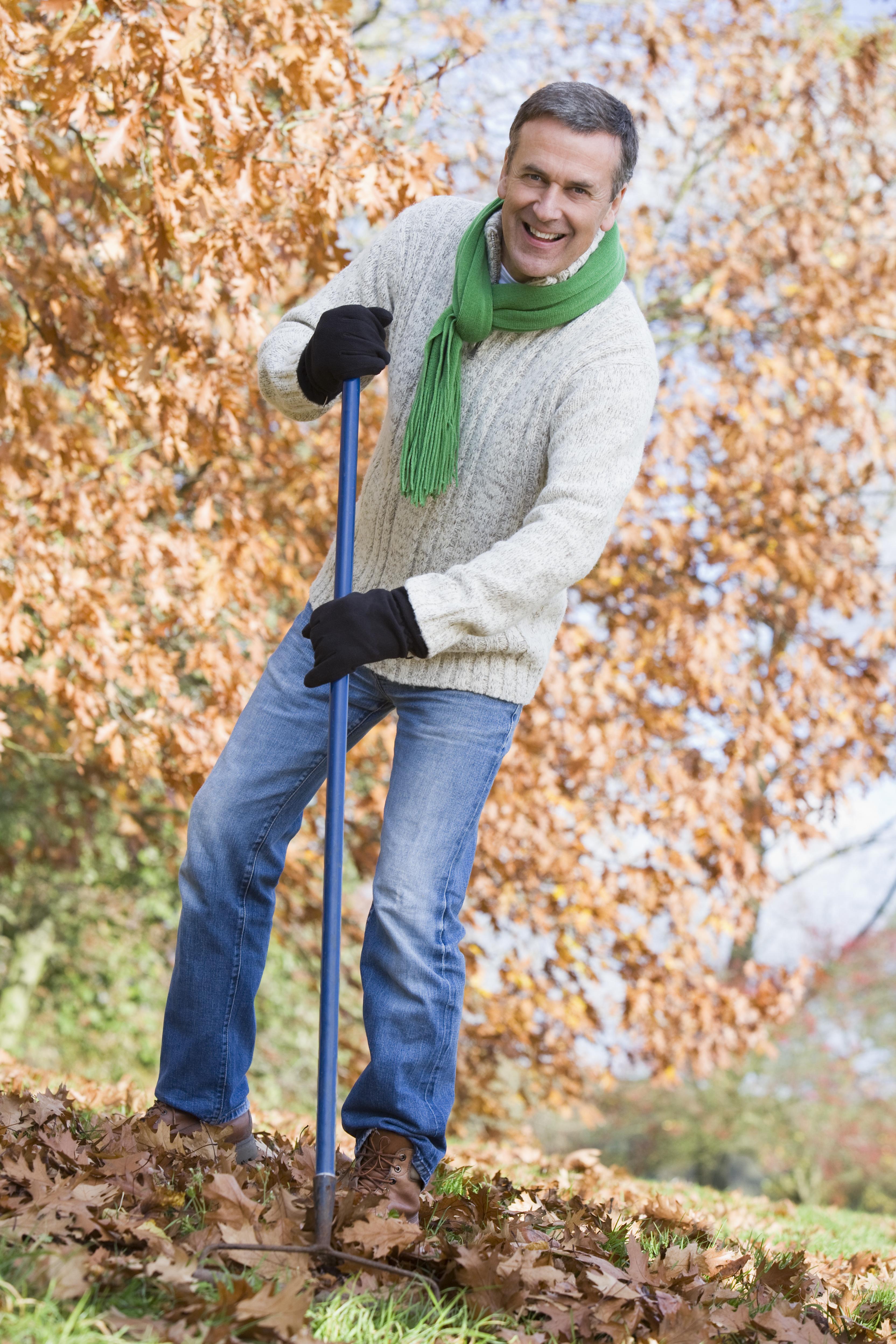 Senior man tidying autumnleaves