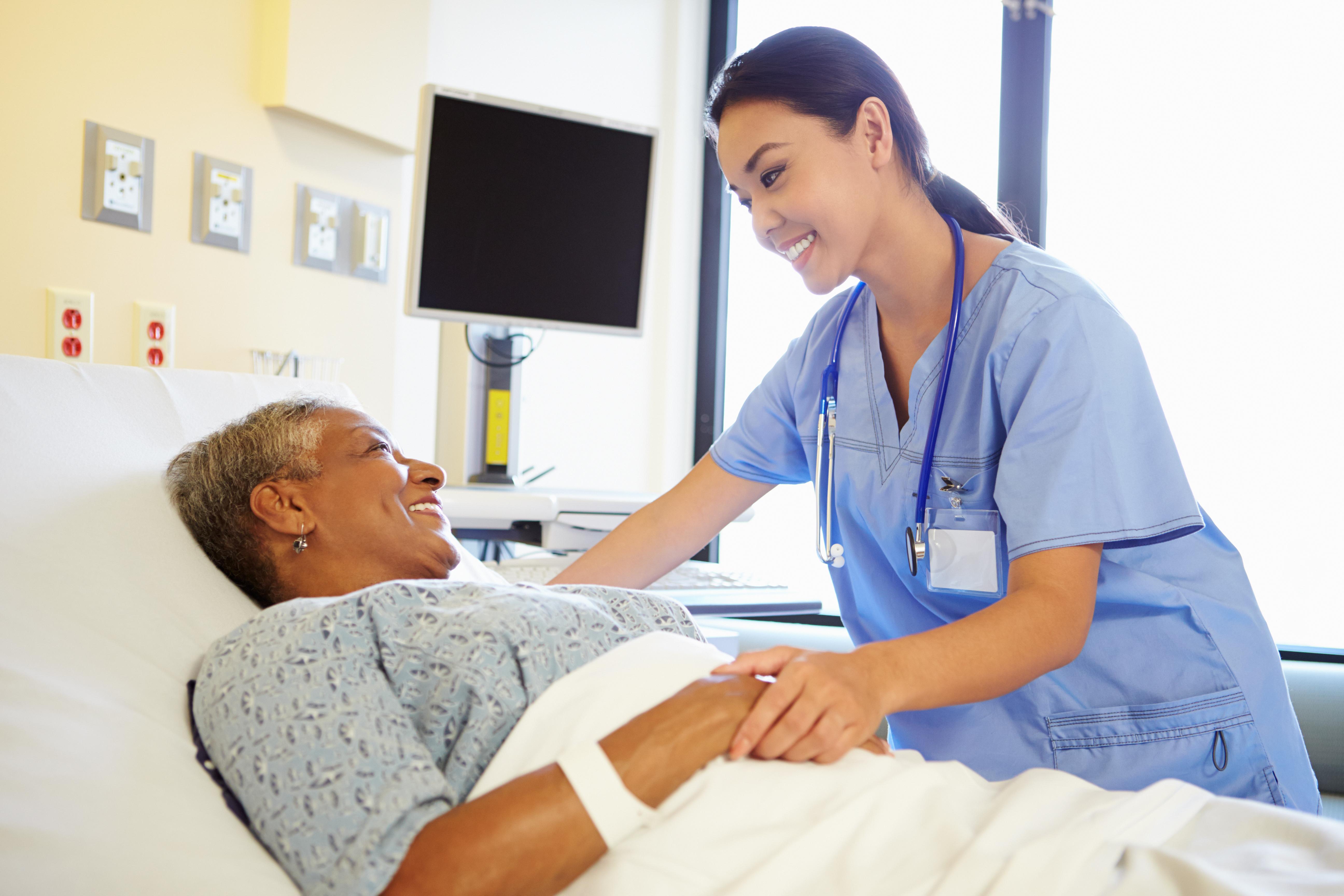 Nurse Talking To Senior Woman In HospitalRoom