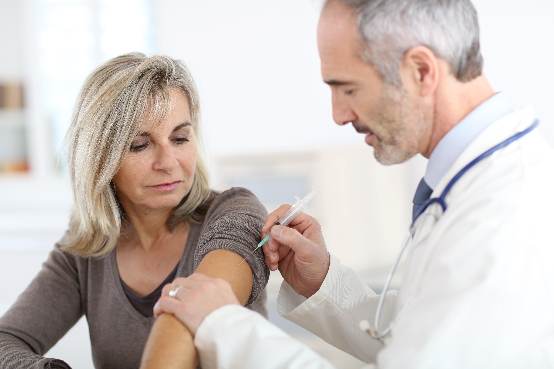 Doctor injecting vaccine to seniorwoman