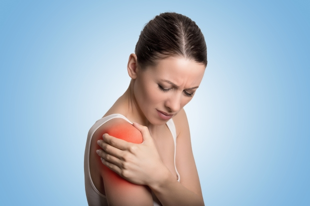 Young woman patient in pain having painful shoulder colored in red.